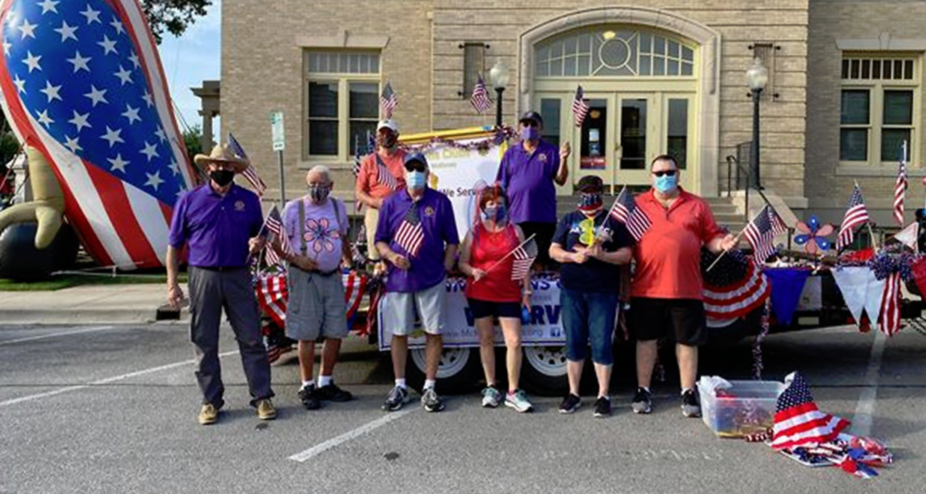 A photo of a group of masked Lions Club members standing in front of a decorated float for a public event